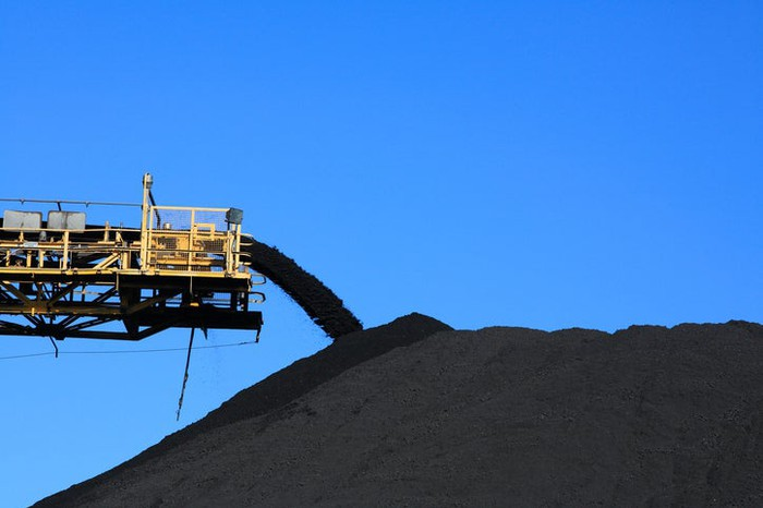 A conveyor system adding coal to a large pile.