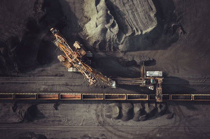 An overhead view of a coal mining operation loading product onto freight cars.