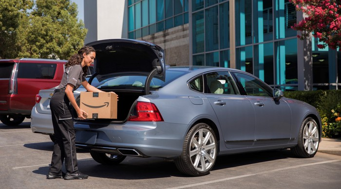An Amazon delivery person is shown placing a package in the trunk of a 2018 Volvo S90 sedan. The sedan is parked in a corporate parking lot, and its trunk lid is open.