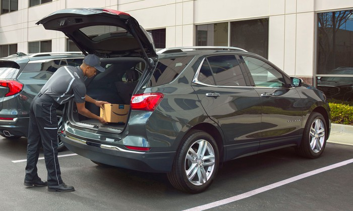 An Amazon delivery person is shown placing a package in the back of a 2018 Chevrolet Equinox crossover SUV. The vehicle is in a corporate parking lot, and its rear liftgate is open.