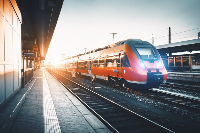 Modern high-speed red commuter train at a railway station.