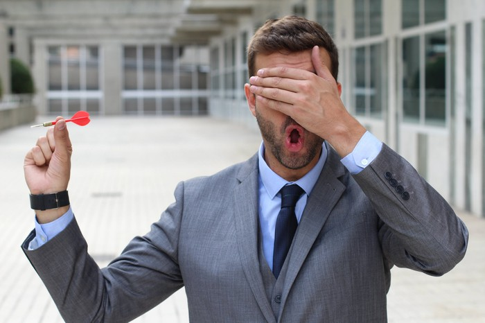 Businessman with hand over his eyes about to throw a dart.