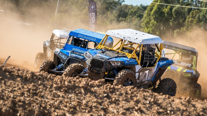 Several off-road vehicles with Polaris logos on a muddy track racing.