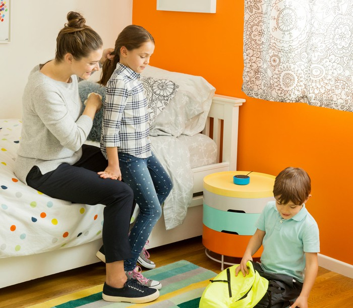 A fmaily sits in a bedroom with an Echo Dot for Kids.
