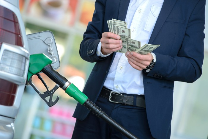 A person in a suit counting money while filling up a gas tank.