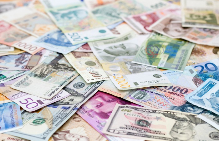 Large spread-out pile of various types of currency from different countries.