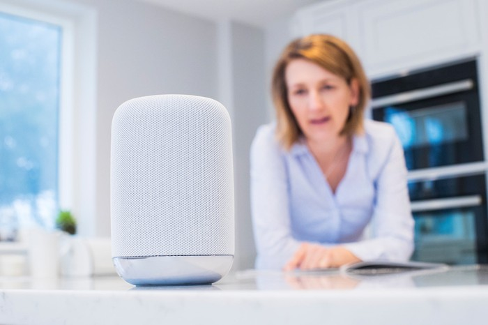 A woman looks at a digital assistant.