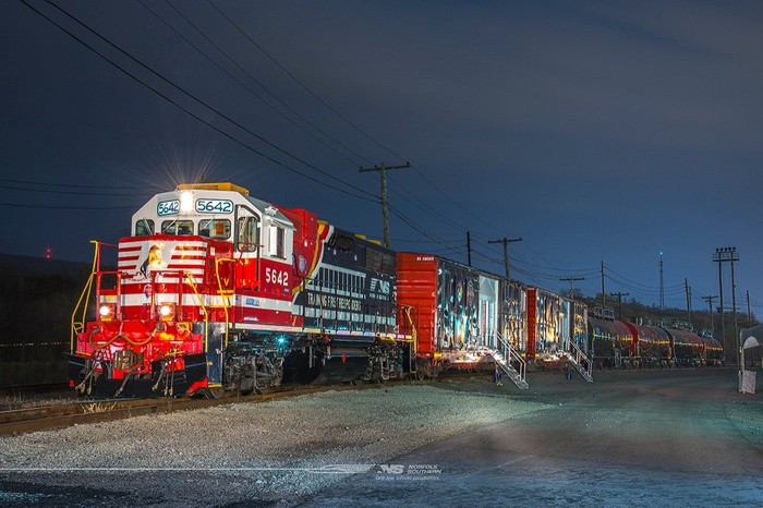 Train at night led by well-lit red locomotive engine.