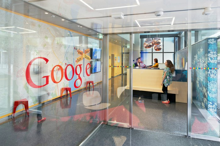 Office entrance with Google logo on transparent wall.