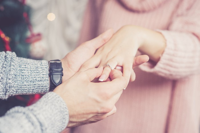 closeup of a man putting an engagement ring on fiance's hand.