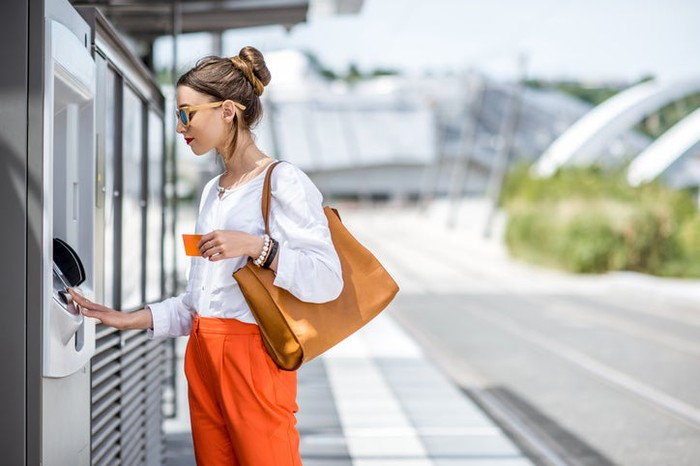 Young woman using ATM machine outdoors at a public transit station.