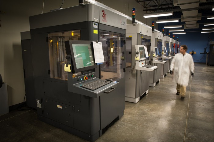 A worker walking by a row of industrial 3D printers in a Proto Labs' facility.