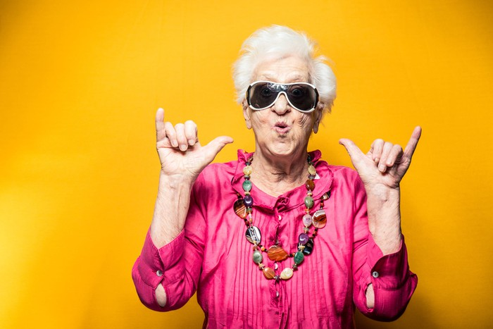 "An older woman wearing a pair of sunglasses and making ""hang loose"" hand signs"