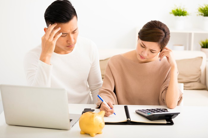 Couple Looking At Notebook With Calculator And Laptop