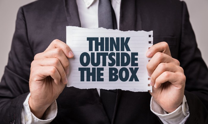 A man holds a paper that says think outside the box.