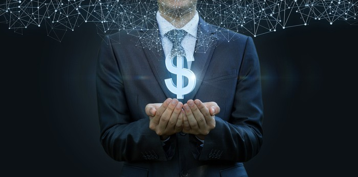 Man in business suit with his hands cupped beneath a glowing money sign that has dots hovering on top of it.
