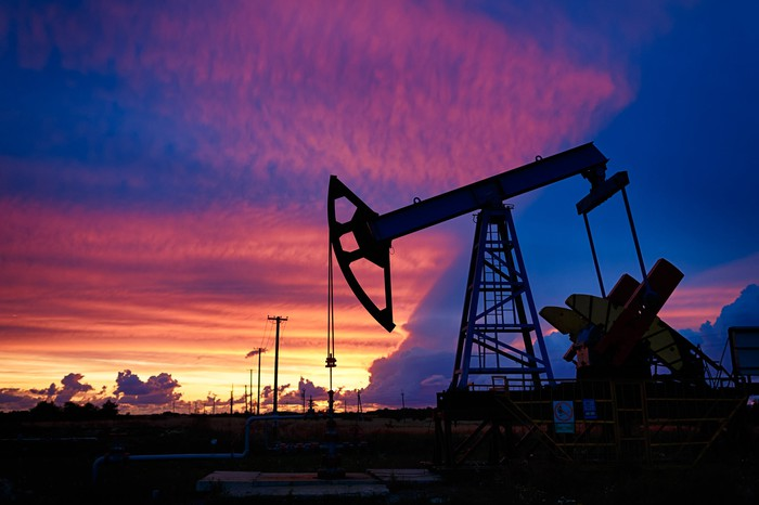 An oil pump with a beautiful sunset in the background.
