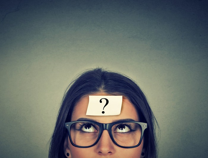 Woman with Post-it not on her head with a question mark on it.
