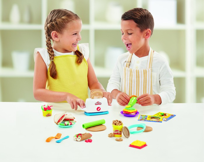 A girl and a boy playing with Play-Doh.