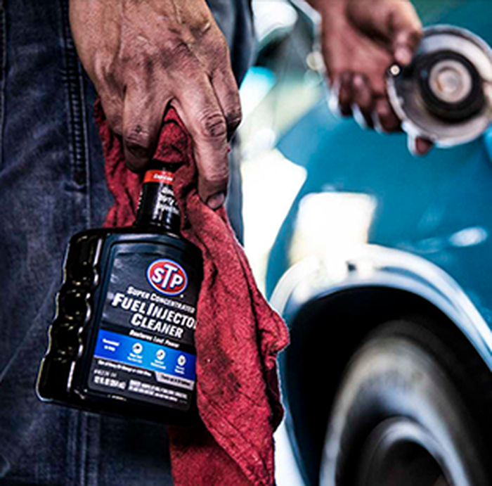 A man's hand is holding a spray bottle of STP fuel injection cleaner his another hand is shown holding a car's gas cap open.