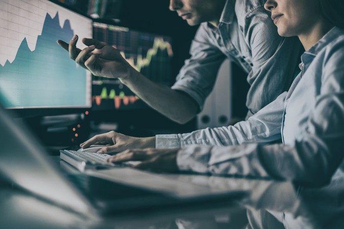 A man and a woman looking at a computer screen with a stock chart on it.