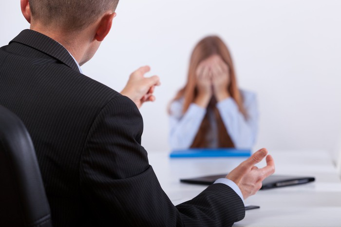 Woman covering her face while man in suit sitting across from her points a finger her way