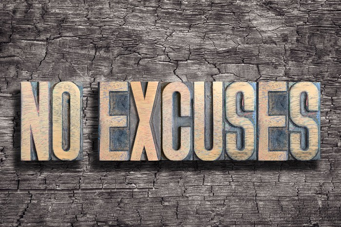 The words No Excuses in gold lettering on a wooden background.
