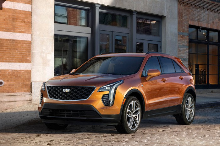 A copper-colored 2019 Cadillac XT4, a compact crossover SUV, parked in front of a commercial building.