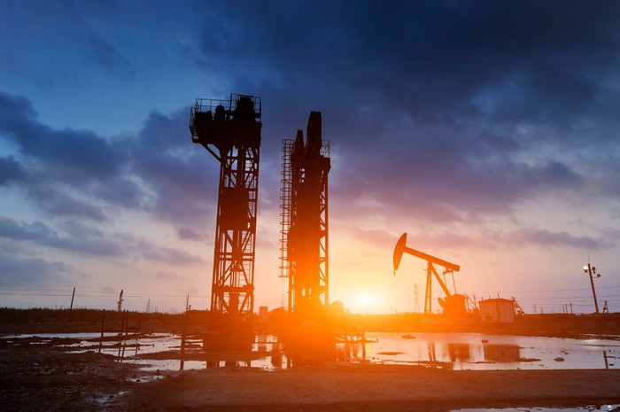 Oil drilling rigs and an oil pump jack with the sun setting in the background.