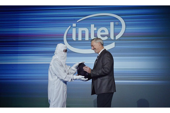 An Intel executive and an engineer holding a silicon wafer in front of a big Intel logo.