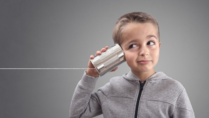 Child holding a can with a string attached to it up to his ear.