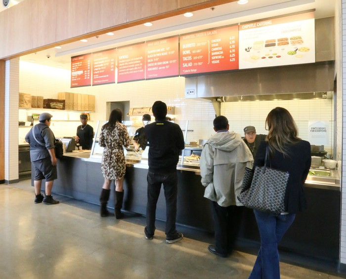 People line up to order at a Chipotle.