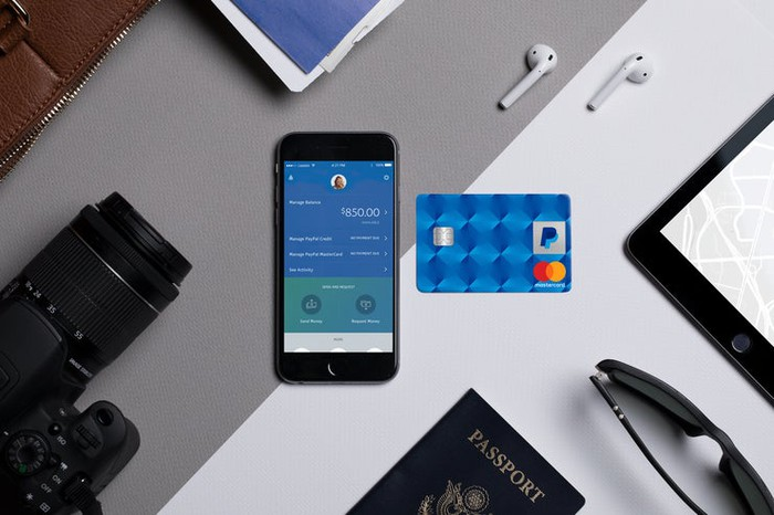 PayPal Cashback Mastercard surrounded by travel items: music ear buds, camera, mobile phone, passport, etc.