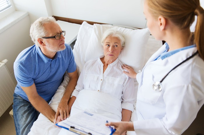 Older woman in hospital bed being checked on by female doctor with older man at her side