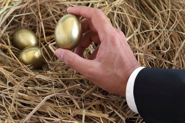 Close-up on businessman's hand, picking up one of three golden eggs from a straw nest.