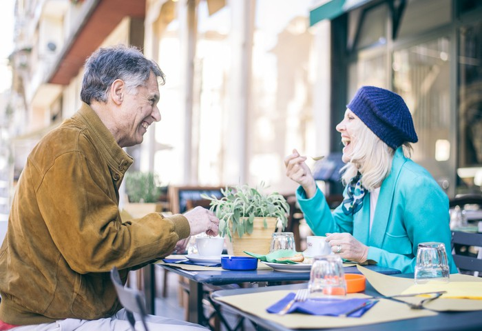 Older couple eating at an outdoor restaurant