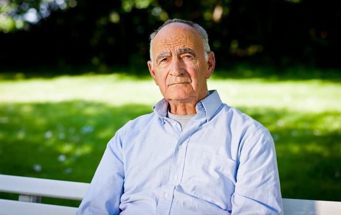 Older man sitting outdoors, looking sad