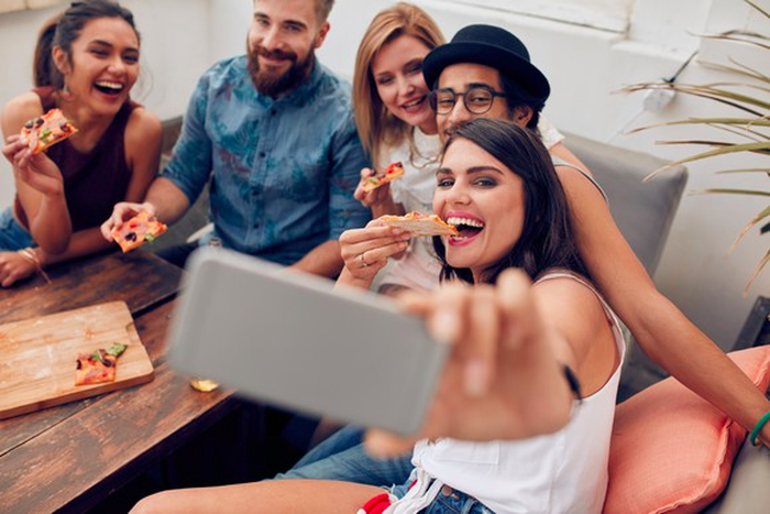 A group of young adults take a selfie on a couch while they're eating pizza