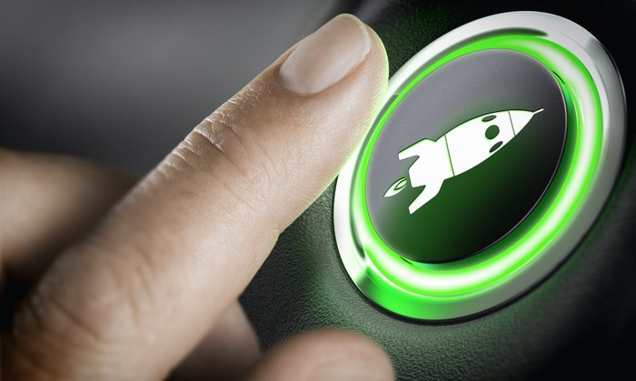 Finger reaching to press a green lighted button depicting a rocketship.