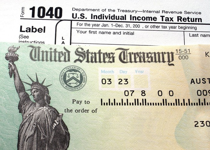 Tax refund check on top of a 1040 tax form.