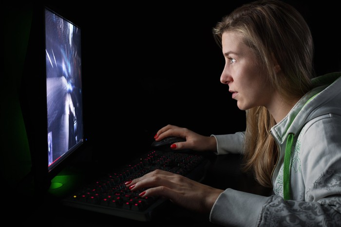 Woman playing video game stares intently at screen