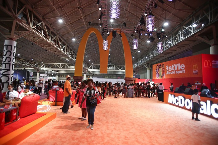 McDonald's logo hanging from ceiling at convention center, with McDonald's booth nearby.