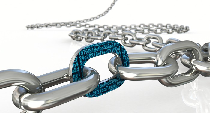 A steel chain laid across a plain white table, with one link covered in hexadecimal data strings.