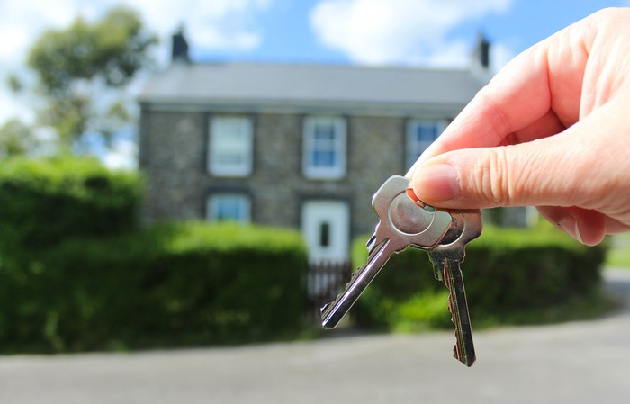 Hand holding two keys in the foreground of a two-story home.