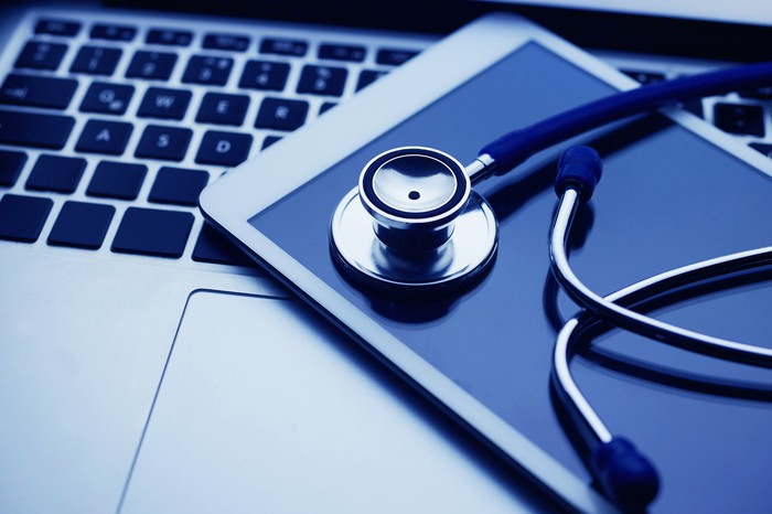 Stethoscope on smartphone on top of a laptop