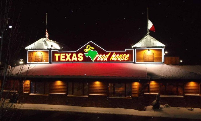 The exterior view of a Texas Roadhouse store at night. The company's state of Texas logo is displayed on top of the building.
