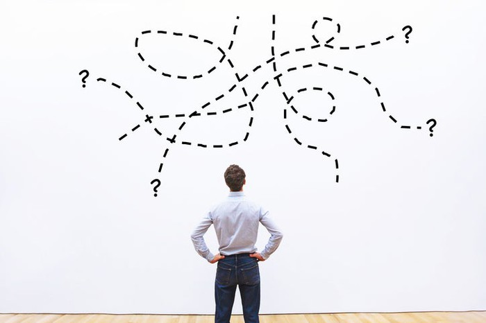 A businessman staring at question marks drawn on the wall in front of him.