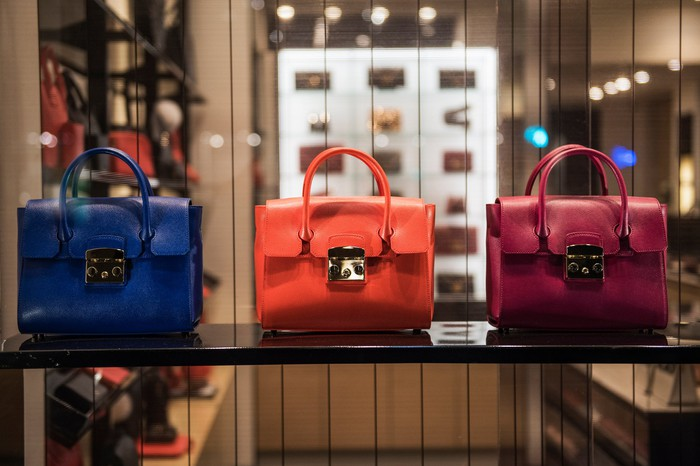 Blue, orange, and purple handbags on display.