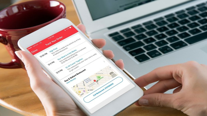 A person holds out their smartphone with information from the Grubhub app on it.