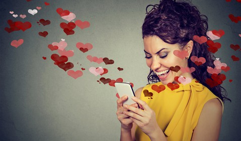 woman looking at phone with hearts coming out